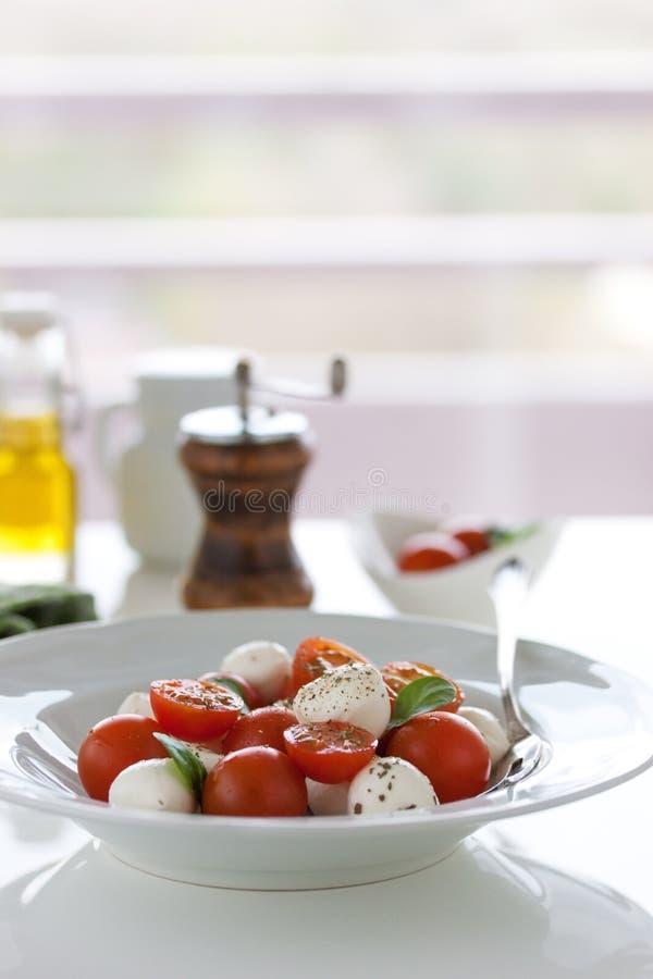 Mozzarella med tomater, italienska örter och salladsidor på en vit platta på en tabell arkivfoton