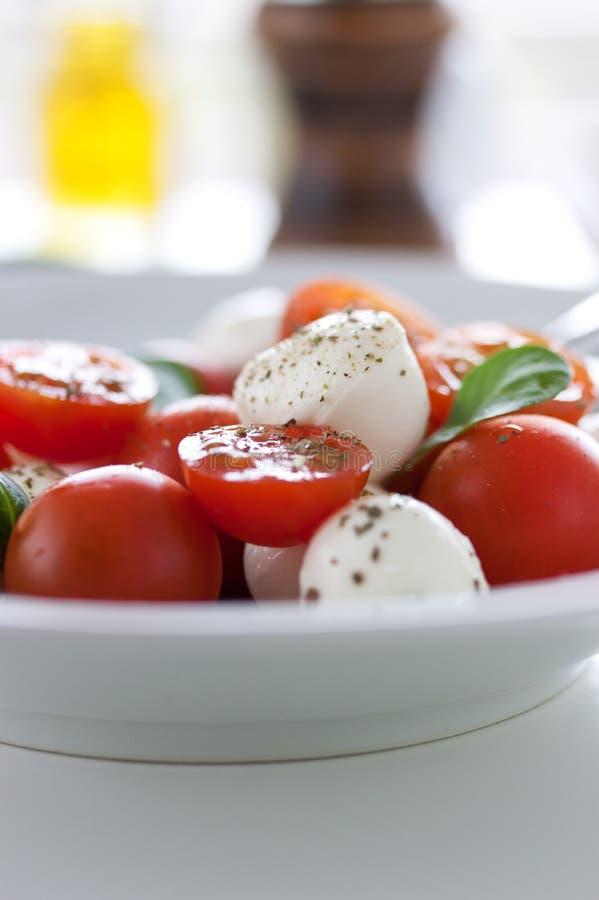 Mozzarella med tomater, italienska örter och salladsidor på en vit platta på en tabell arkivbild