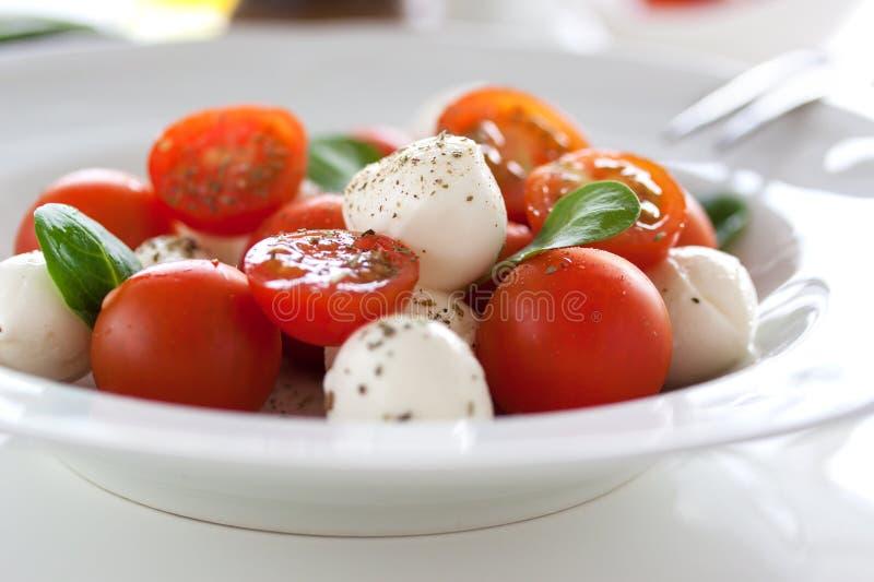 Mozzarella med tomater, italienska örter och salladsidor på en vit platta på en tabell royaltyfria foton