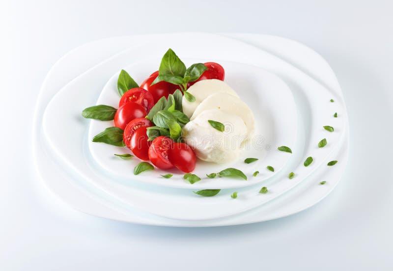 Mozzarella mit Tomate und Basilikum lizenzfreie stockfotos