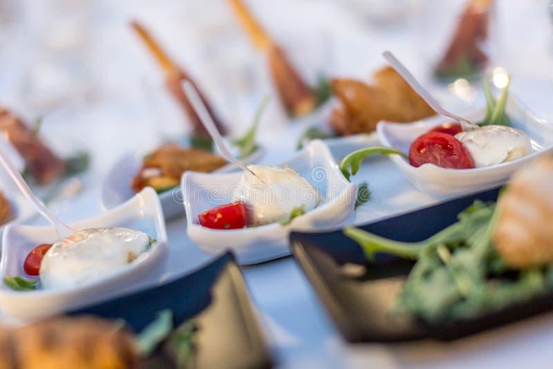 Mozzarella- och tomatapetizrar serverade i en vit liten platta under brunch food buffet royaltyfri fotografi
