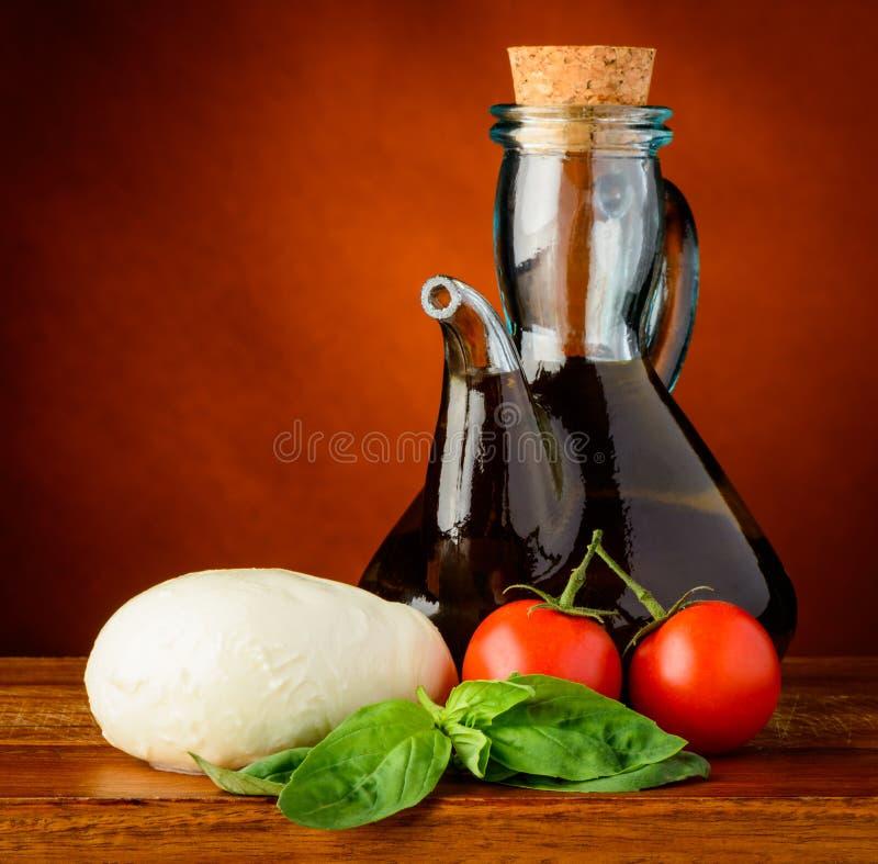 Mozzarella, olivolja, basilika och tomater fotografering för bildbyråer