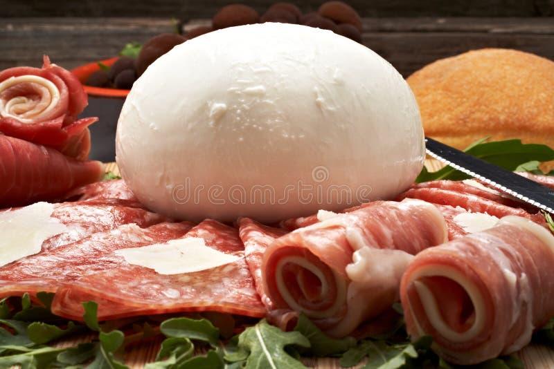 Mozzarella and pepperoni. Italian bufala mozzarella with pepperoni on chopping board royalty free stock images