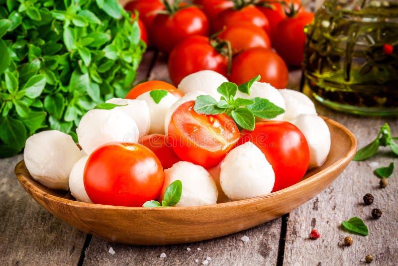 Mozzarella, pomodori ciliegia organici, basilico fresco e olio d'oliva fotografie stock libere da diritti