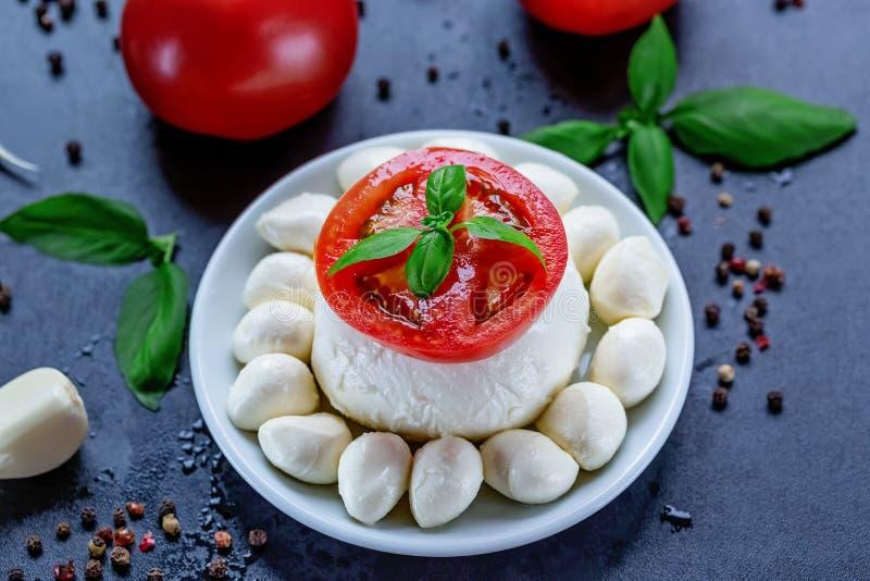 Mozzarella, rote Tomaten und frischer Basilikum auf einem schwarzen Hintergrund Beschneidungspfad eingeschlossen Flache Lage Chef lizenzfreie stockfotos