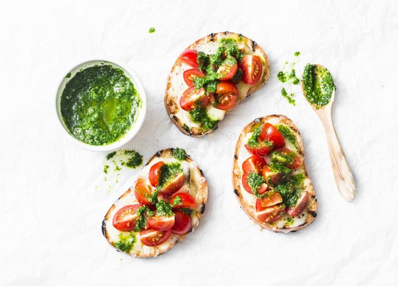 Mozzarella ser, czereśniowi pomidory i arugula pesto bruschetta na lekkim tle, odgórny widok Arugula pesto i kanapki - smak zdjęcia stock