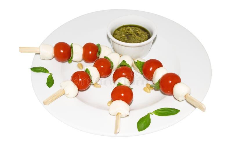 Mozzarella, tomates de cereja, pesto e manjericão imagem de stock royalty free