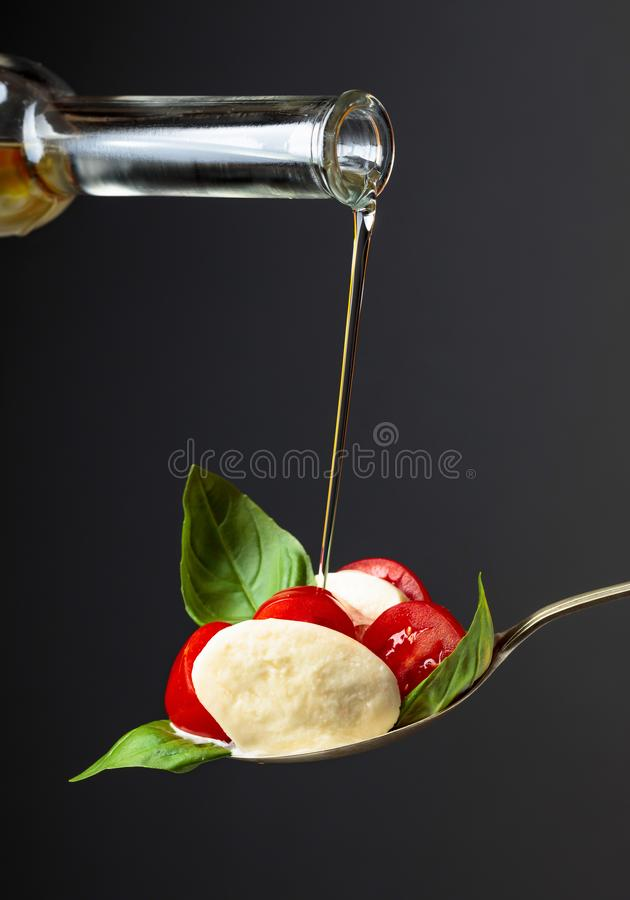 Mozzarella with tomato, basil and olive oil on a dark background stock images