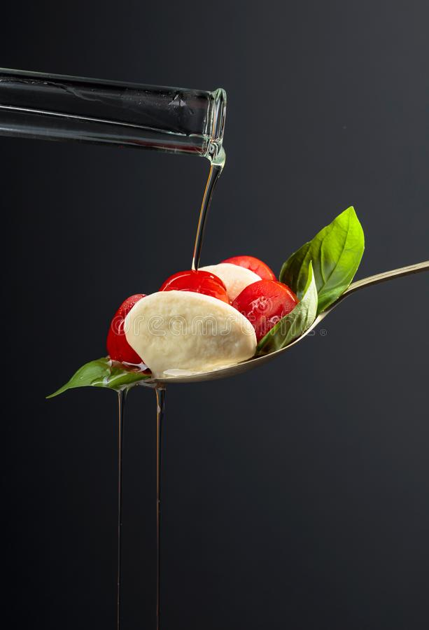 Mozzarella with tomato, basil and olive oil on a dark background royalty free stock image
