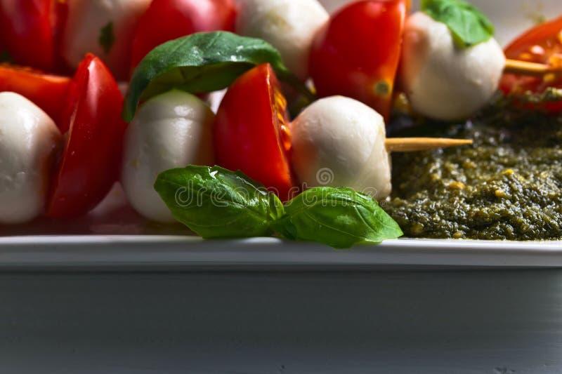 Mozzarella with tomato , basil and pesto sauce. On a kitchen table royalty free stock image