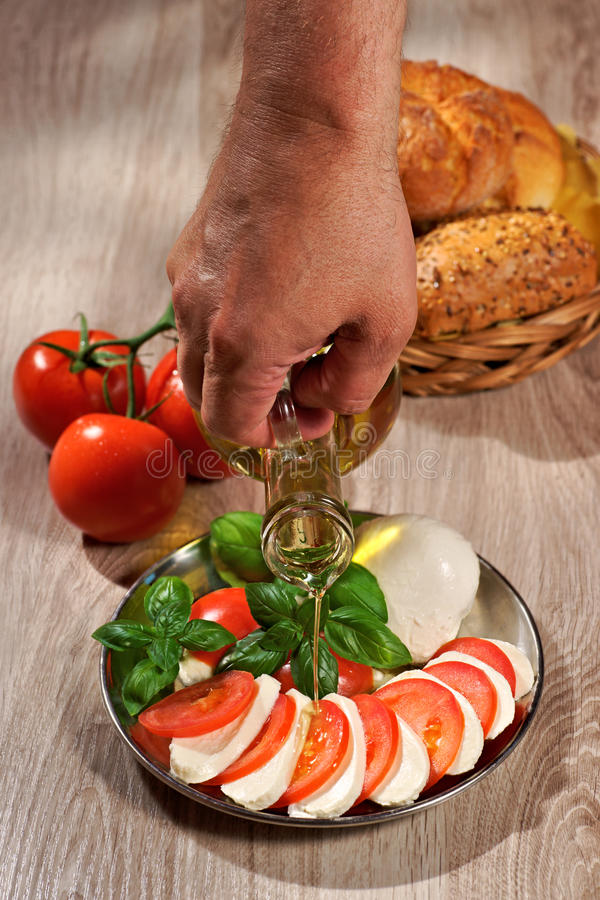 Mozzarella, tomatoes, olive, basil, roll, human hand pouring olive from a bottle stock photo