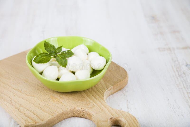 Mozzarella in un piatto verde su una tavola di legno C fresca deliziosa immagini stock libere da diritti