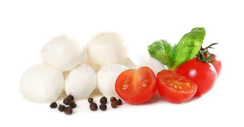 Mozzarellaostbollar, körsbärsröda tomater och basilika på vit bakgrund arkivbild