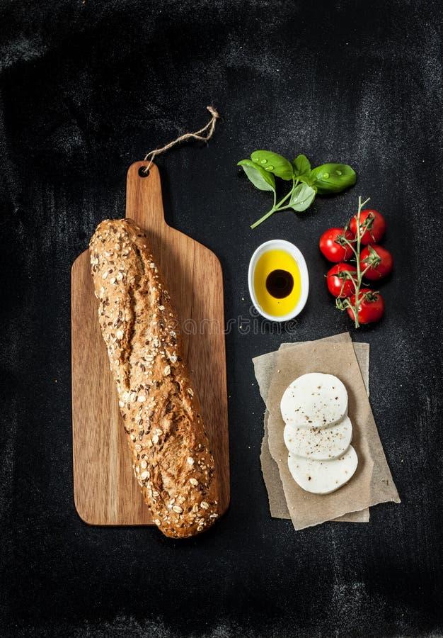 Mozzarellaostsmörgåsrecept - ingredienser på svart arkivfoton
