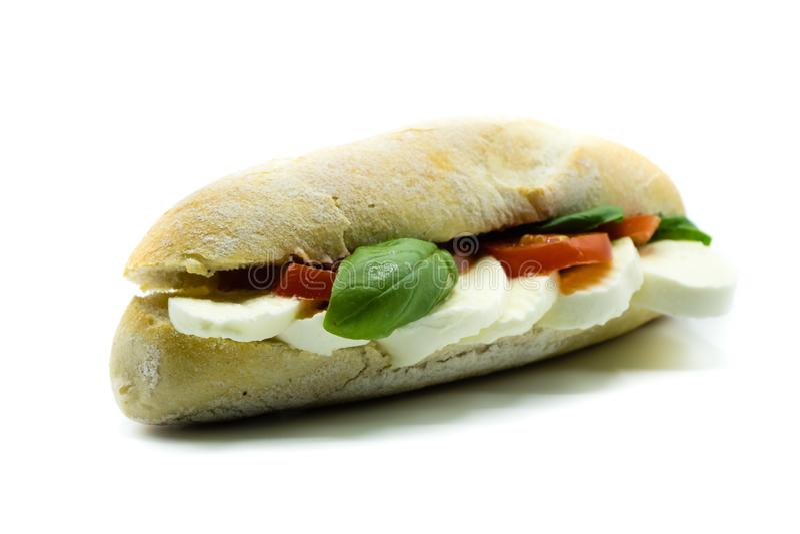Mozzarelli pomidorowy baguette z basilem odizolowywającym na białym tle zdjęcia stock