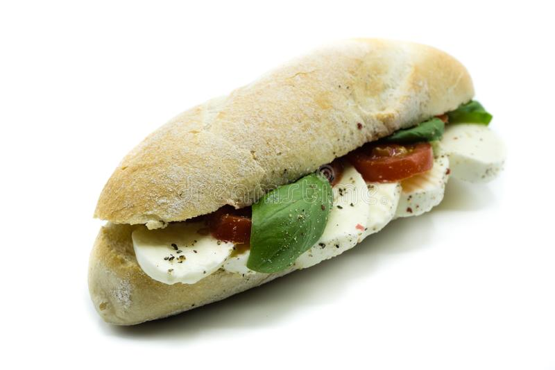 Mozzarelli pomidorowy baguette z basilem odizolowywającym na białym tle obrazy stock