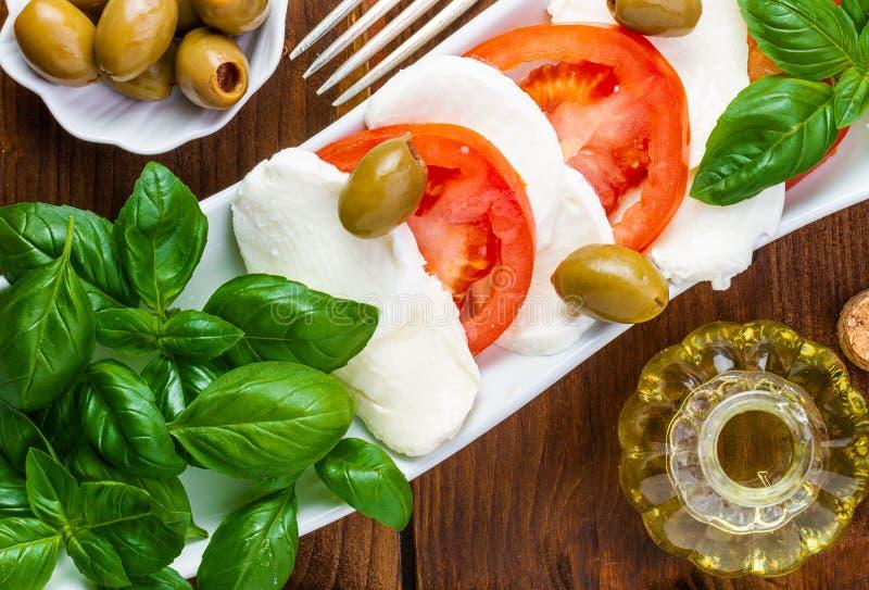 mozzarelli ?wie?a sa?atka Mozzarella z pomidorami i basilem bean og?rki s? sma?one szpik?w kostnego ?wie?ych pomidor?w jarskich c zdjęcie stock