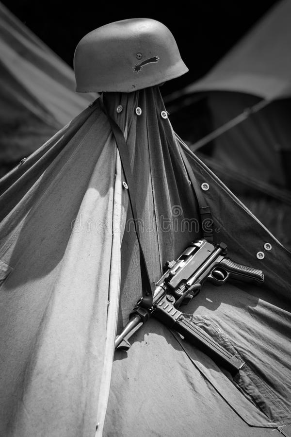 MP-40 and Helmet Hanging on a Tent. MP-40 and helment hanging on a tent in a camp, in black and white stock photography