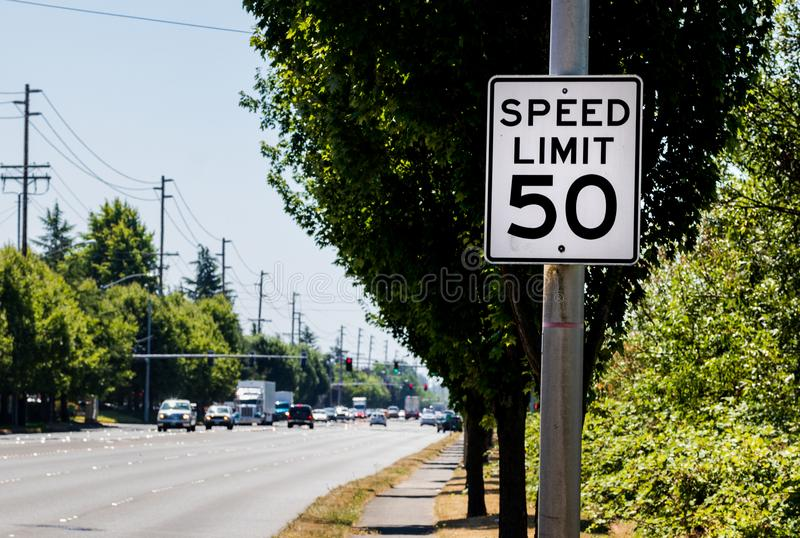 50 mph speed limit sign on post with a road and tree stock image