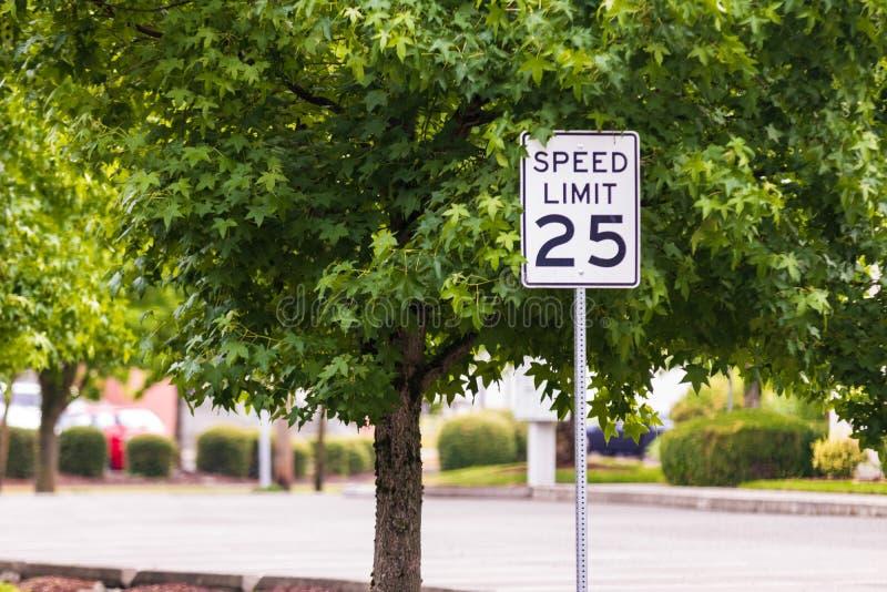 MPH-Zeichen mit einem Baum und einer Betonstraße lizenzfreie stockfotografie