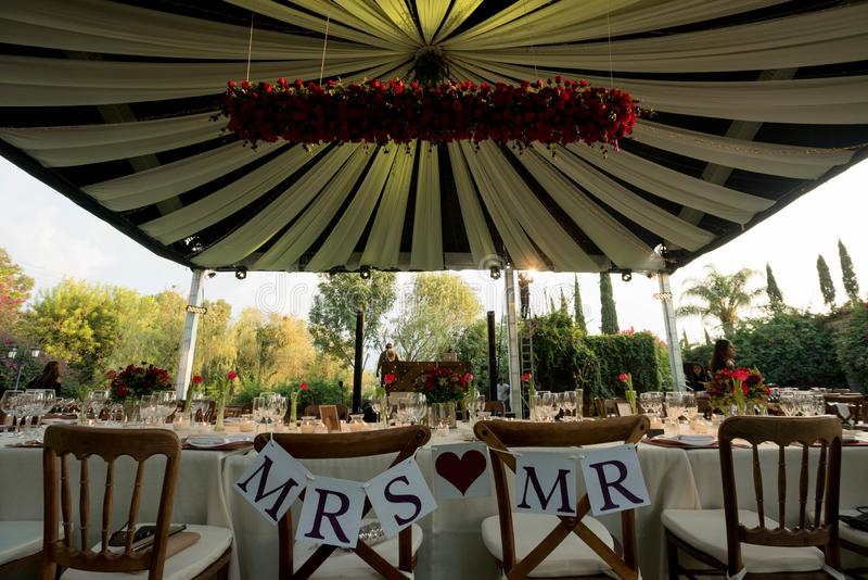 MR and MRS chairs for bride and groom at wedding decoration with luxury wedding awning decorated with natural flowers royalty free stock image
