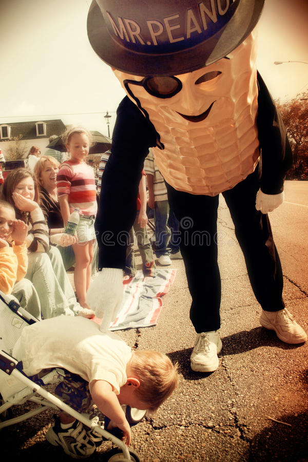 Mr. Peanut and a scared toddler. Mr. Peanut character scares a toddler boy at a parade in Alabama stock image