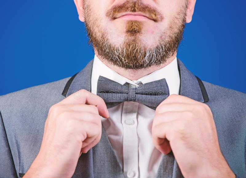 Mr. Perfection. Man adjusting bow tie. business in modern life. illusionist. Bride groom ready for wedding. businessman. In bow tie. man in formal suit. esthete stock image
