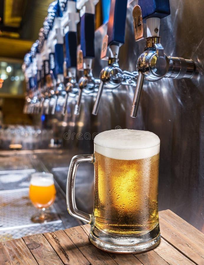 Mroźny kubek lekki piwo na starym drewnianym stole Karczemny wnętrze i bar odpierający z piw klepnięciami przy tłem fotografia stock