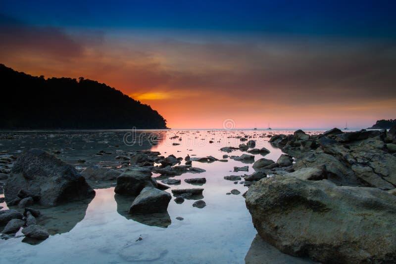 Mroczny czas po zmierzchu na plaży z kamieniem obraz stock