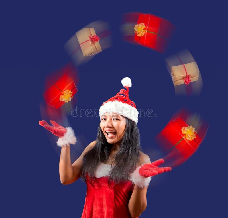 mrs Claus ser kameran och jonglerar med julgåvor arkivbilder