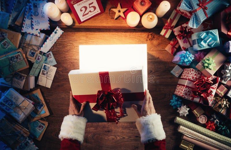 Mrs Sankt, die einen Geschenkkasten öffnet lizenzfreies stockbild