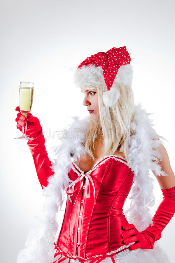 Mrs. Santa looking at champagne glass royalty free stock photo