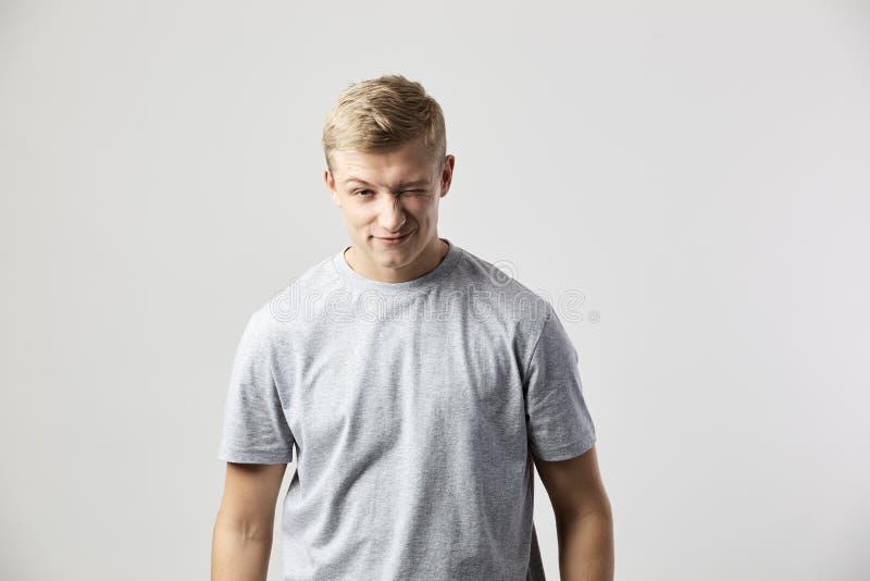Mrugający blond faceta ubierał w koszulki białych stojakach na białym tle w studiu fotografia royalty free