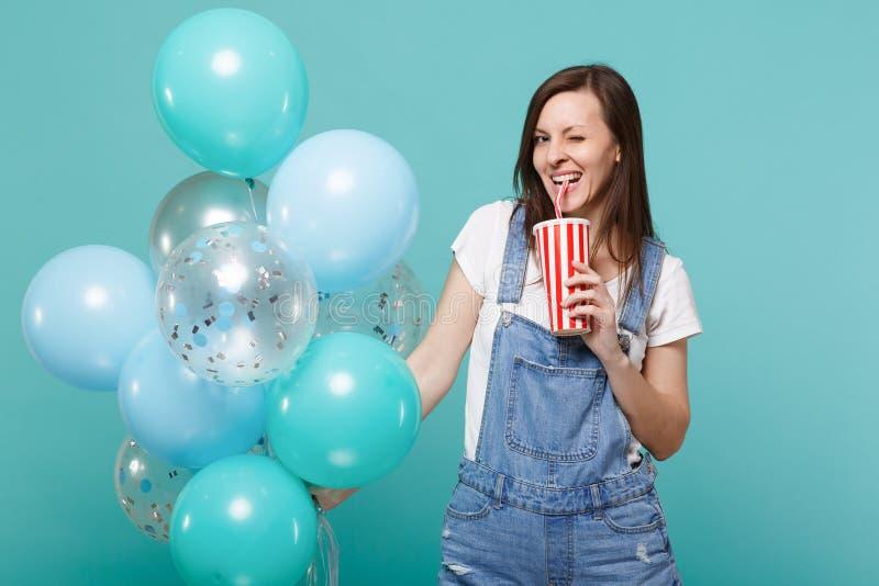Mruganie młoda kobieta w drelichu odzieżowego mienia plastikowej filiżance koli lub sody odświętność z kolorowymi lotniczymi balo fotografia stock