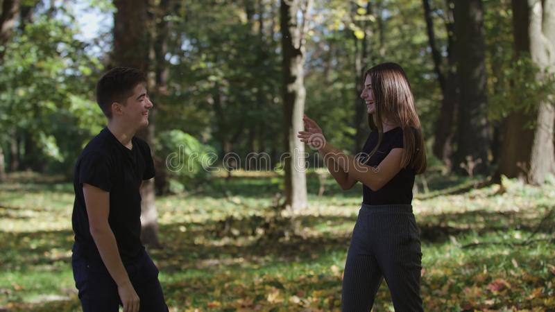 MS Boy and girl jumping and throwing dry leaves in park stock images