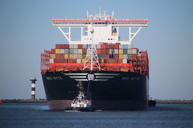 Ms Ditte som för behållareskytteln ankommer på den Maasvlakte hamnen i porten av Rotterdam, drog med det lilla bogserbåtskeppet arkivbilder