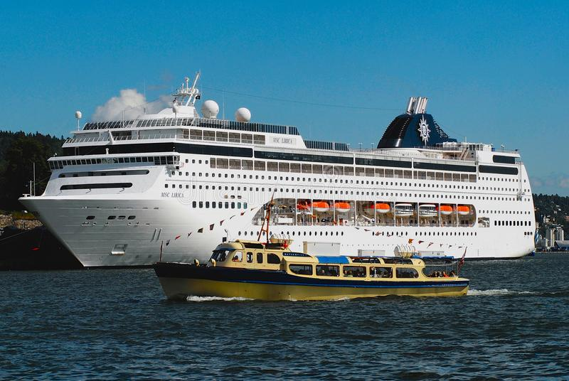 MSC Lirica cruise ship in the sea port of Oslo city with the local ferry boat at the foreground in in Oslo, Norway. royalty free stock photography