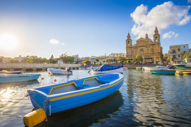 Msida, Malta - Blue traditional fishing boat with the famous Msida Parish Church royalty free stock image