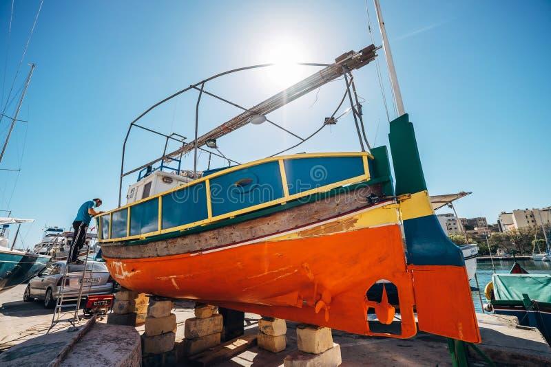Msida, Malta - 30 de março de 2018: O trabalhador reparou uma boa do ` s do pescador foto de stock royalty free