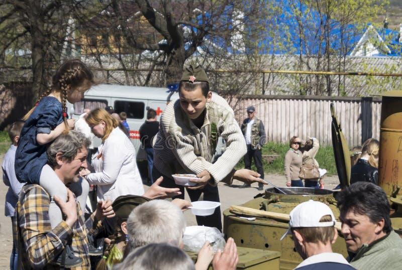 Mstyora, Russia-maggio 9,2015: L'adolescente in cappuccio d'oltremare sovrappone il porridge dalla cucina di campo fotografia stock libera da diritti
