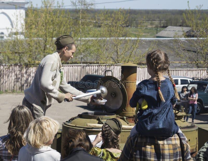 Mstyora, Russie-mai 9,2015 : L'adolescent dans le chapeau d'outre-mer superpose le gruau de la cuisine de champ photo stock