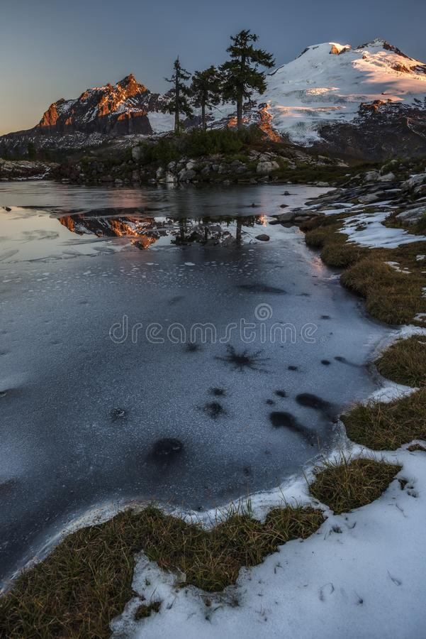 First Light on Snowy Volcano with Reflection in Icy Tarn. Mt Baker and the Black Buttes Reflect in the Still Waters of an Icy Tarn on a Clear Morning in Early stock photo