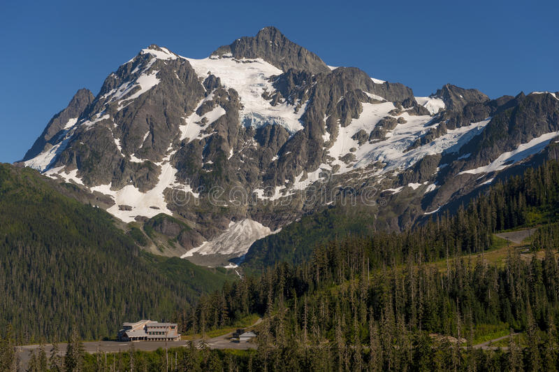 Mt. Baker Ski Area. White Salmon Lodge is dwarfed by Mt. Shuksan during a glorious summer day in the Mt. Baker Recreation area, Washington State stock photography
