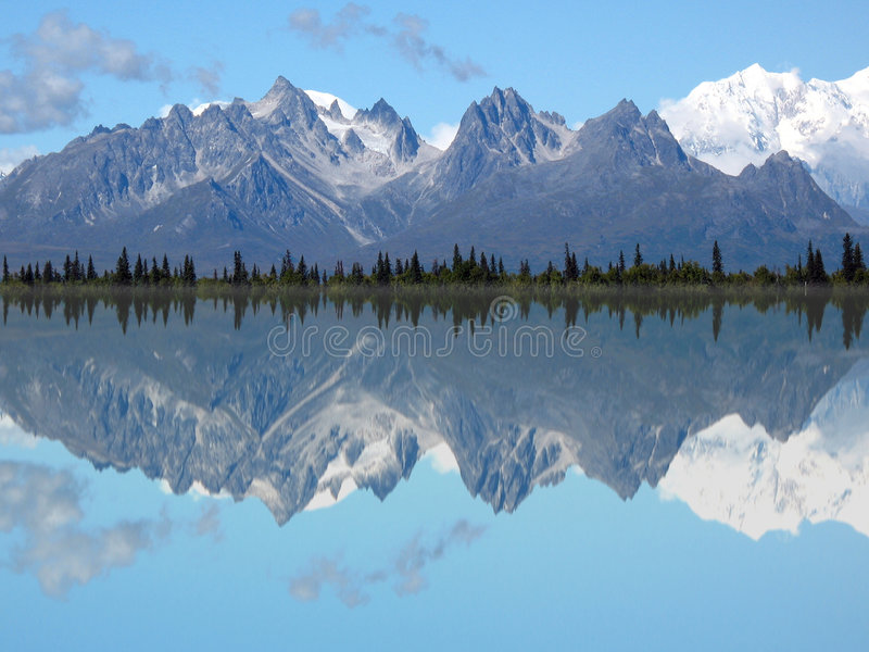 Mt. Foraker and Grand Tokosha Reflection in a Lake. The striking, jagged peaks of the Roostercomb and Mt. Foraker in Denali Park are reflected into a calm lake royalty free stock photos