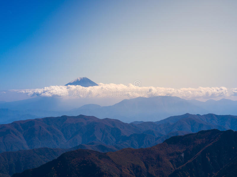 Mt. Fuji through the dense shiny cloud with the blue sky. Captured from Kitadake, Minami South Alps, Yamanashi Prefecture, Japan stock photography