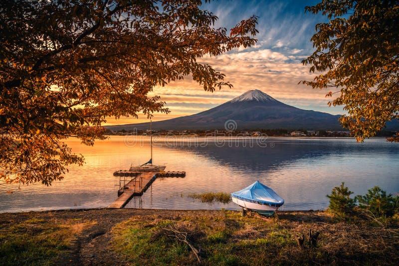 MT Fuji over Meer Kawaguchiko met de herfstgebladerte en boot bij zonsopgang in Fujikawaguchiko royalty-vrije stock afbeelding