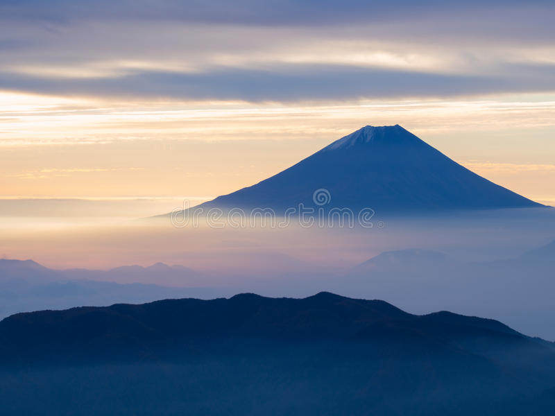 Mt. Fuji over the mist after sunrise. Mt. Fuji over the mist with the overcast sky after sunrise in the morning, captured from Kitadake, Minami South Alps royalty free stock photography