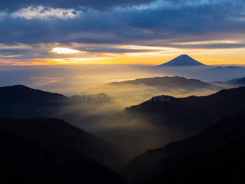 Mt. Fuji over the mist after sunrise. Mt. Fuji over the mist with the overcast sky after sunrise in the morning, captured from Kitadake, Minami South Alps royalty free stock photos