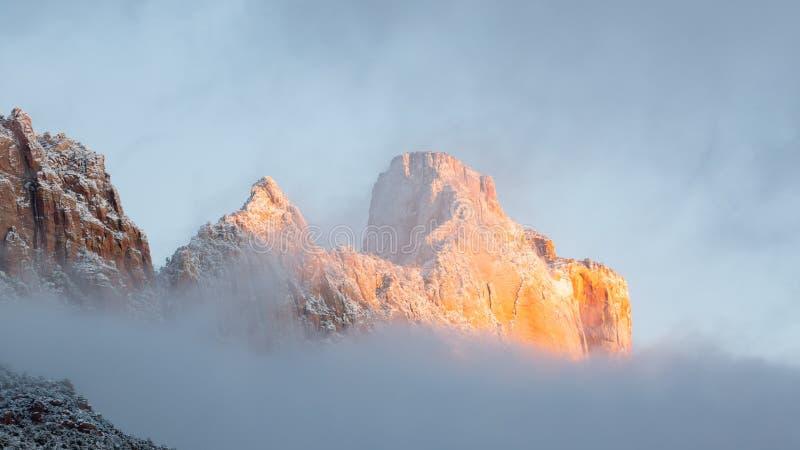 Mt Kinesava in Nationalpark Zion hat eine frische Schicht des Schnees und ein Leichentuch von Wolken als der Morgensonne malt die stockfoto