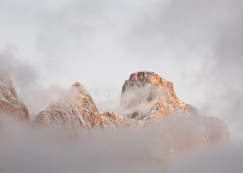 Mt. Kinesava is shrouded in clouds with the snow covered peaks breaking through in the soft light before sunrise royalty free stock photo